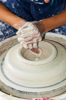 cwizner blue hands making bowl bottom on wheel